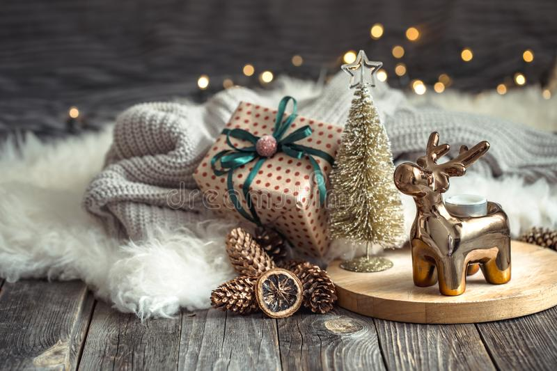 Christmas festive background with toy deer with a gift box and Christmas tree, blurred background with golden lights on wooden. Christmas festive background with royalty free stock photography