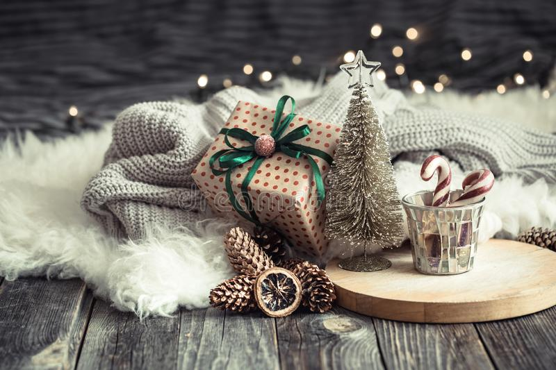 Christmas festive background with toy deer with a gift box and tree, golden lights on wooden deck table. Christmas festive background with toy deer with a gift stock photo