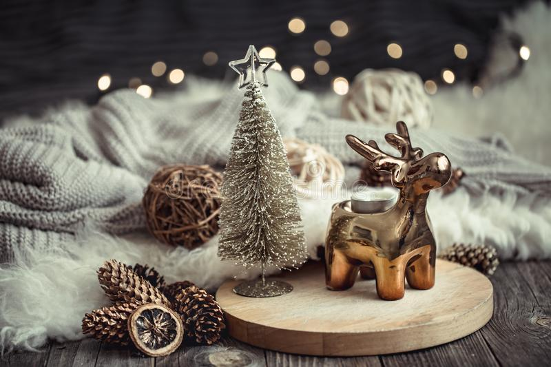 Christmas festive background with toy deer with a gift box and tree, golden lights on wooden deck table. Christmas festive background with toy deer with a gift stock photography