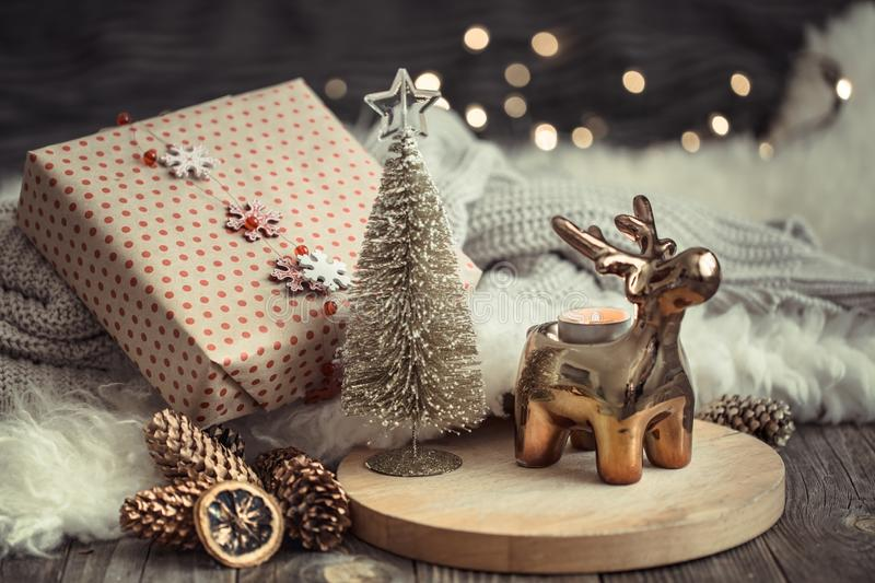 Christmas festive background with toy deer with a gift box and Christmas tree, golden lights on wooden deck table. Christmas festive background with toy deer stock photos