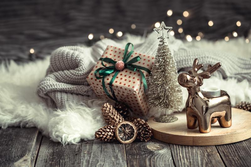 Christmas festive background with toy deer with a gift box and Christmas tree, golden lights on wooden deck table. Christmas festive background with toy deer royalty free stock photography