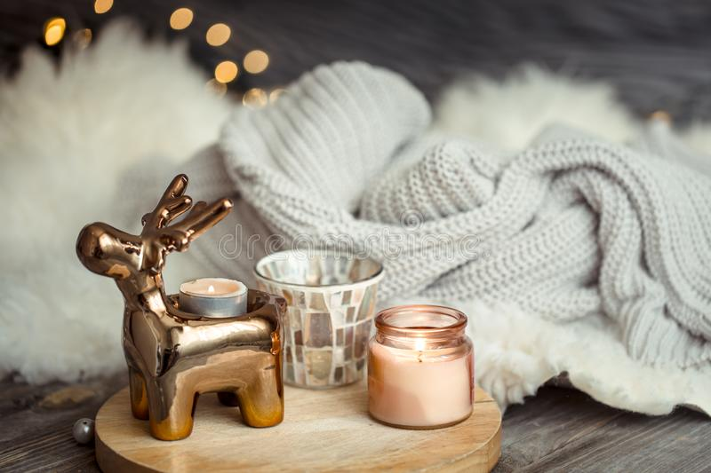Christmas festive background with toy deer, golden lights and candles, wooden deck table. And winter sweater royalty free stock images