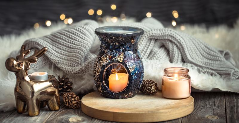 Christmas festive background with toy deer, golden lights and candles, wooden deck table. And winter sweater stock photography