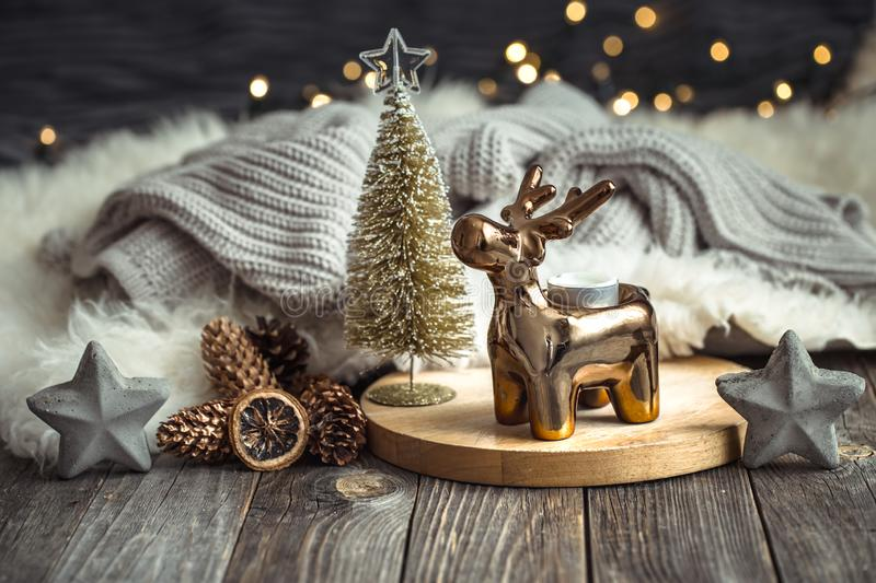 Christmas festive background with toy deer, golden lights and candles, wooden deck table. And winter sweater royalty free stock photo