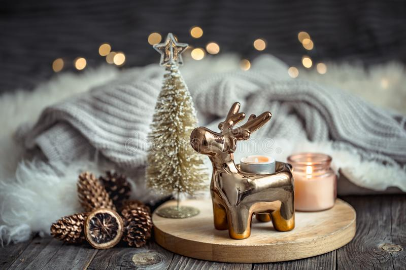 Christmas festive background with toy deer, golden lights and candles, wooden deck table. And winter sweater royalty free stock photos
