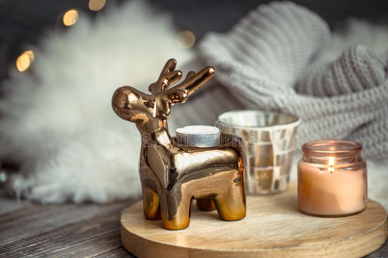 Christmas festive background with toy deer, golden lights and candles, wooden deck table. And winter sweater royalty free stock image