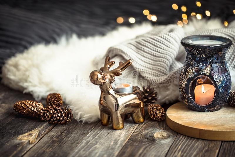 Christmas festive background with toy deer, golden lights and candles, wooden deck table. And winter sweater stock photos
