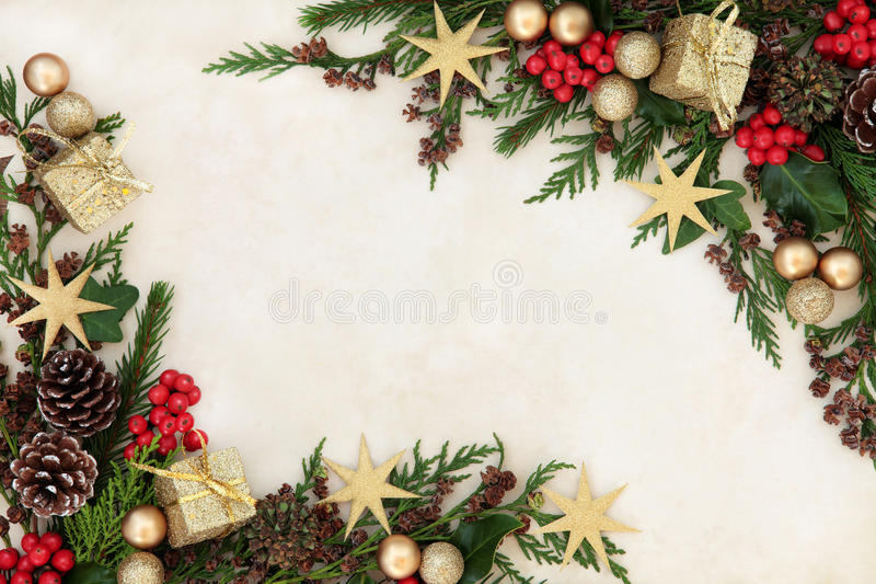Christmas Festive Border. Christmas background border with gold bauble decorations, holly, mistletoe, fir and cedar cypress greenery on old parchment paper royalty free stock images