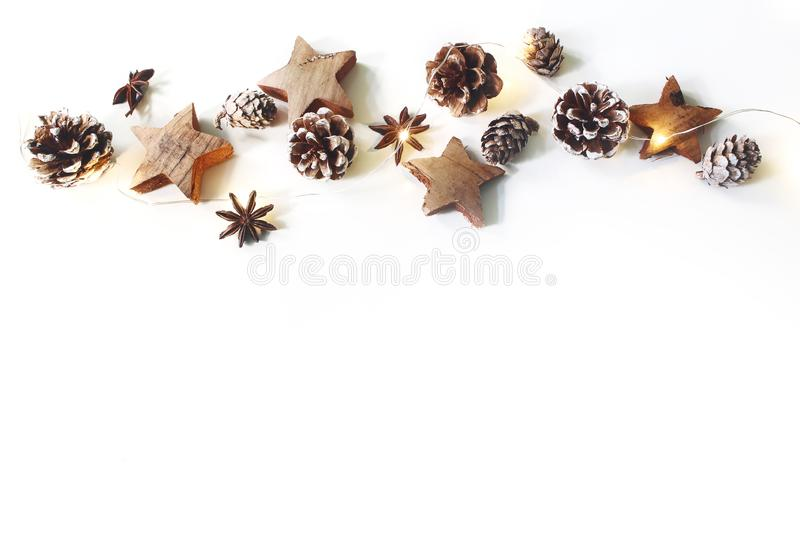 Christmas festive border, banner. Winter arrangement of pine cones, anise, wooden stars and glowing Christmas lights stock photos