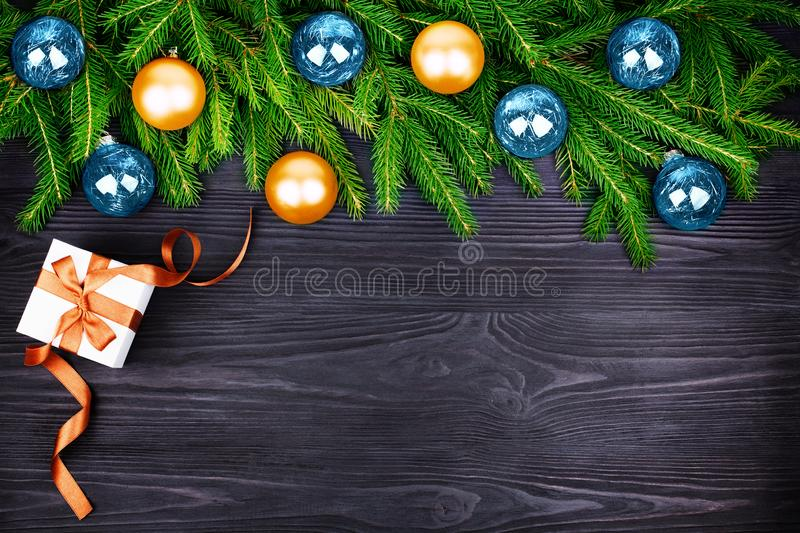 Christmas festive border, New Year decorative frame, golden and blue balls decorations on green fir branches, gift box on black. Christmas festive border, New royalty free stock image