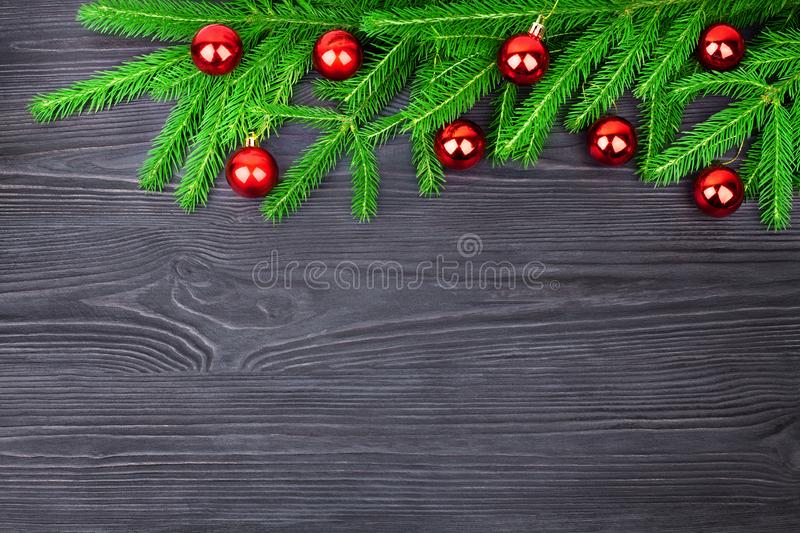 Christmas festive border, New Year decorative frame, shiny red balls decorations on green fir branches on black wooden background royalty free stock images