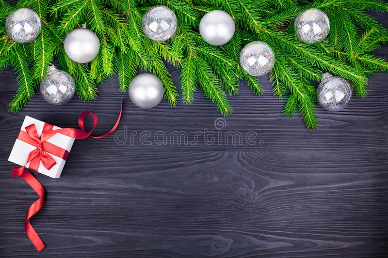 Christmas festive border, New Year decorative frame, shiny silver balls decorations on green pine branches, gift box on black wood royalty free stock photo