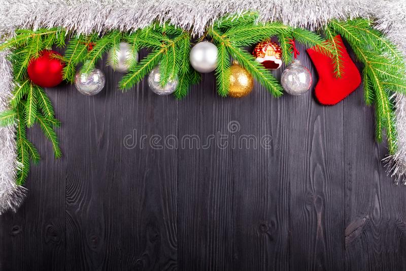 Christmas festive border, New Year decorative frame, silver balls decorations, red gift sock on green pine branches on black wood royalty free stock images