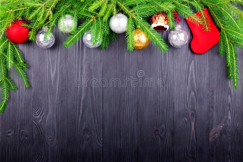 Christmas festive border, New Year decorative frame, silver balls decorations, red gift sock on green pine branches on black wood. En background closeup, winter stock photography