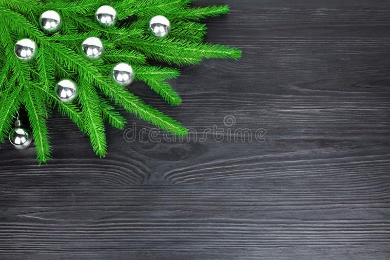 Christmas festive corner border, New Year decorative frame, silver glass balls decorations on green fir branches on black wood royalty free stock photo