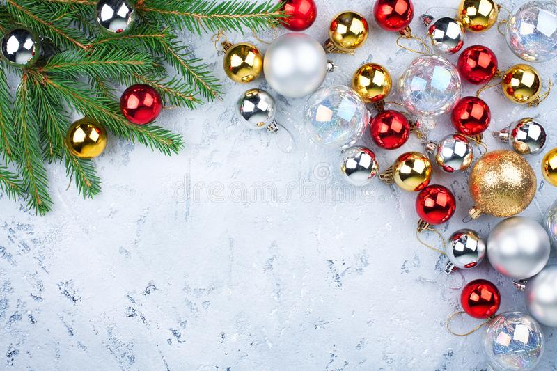 Christmas festive frame, New Year decorative border, shiny gold, silver, red balls decorations on green fir branches on light blue royalty free stock photo