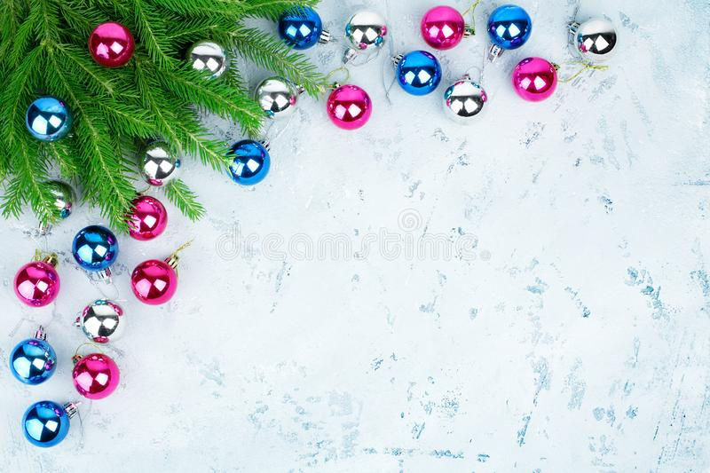 Christmas festive frame, New Year decorative corner border, shiny silver, pink, blue balls decorations, fir branches on light icy stock images