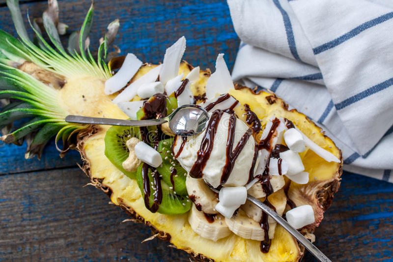 Christmas festive pineapple cut in half with a scoop of ice cream royalty free stock images