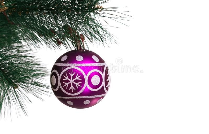 Christmas festive purple balloon with the image of a spruce and snowflakes for decoration hanging on artificial branches of a fir-. Tree on a white background royalty free stock photography