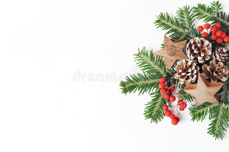 Christmas festive styled floral composition. Pine cones, fir tree branches, red rowan berries and wooden stars on white stock image