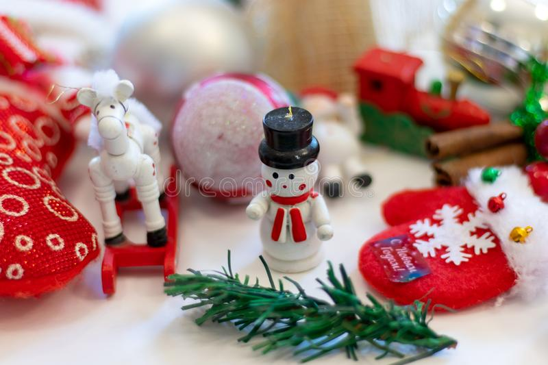 Christmas figure on the Christmas tree. White snowman in a black hat. Horse Christmas ball red with silver Christmas tree. stock image