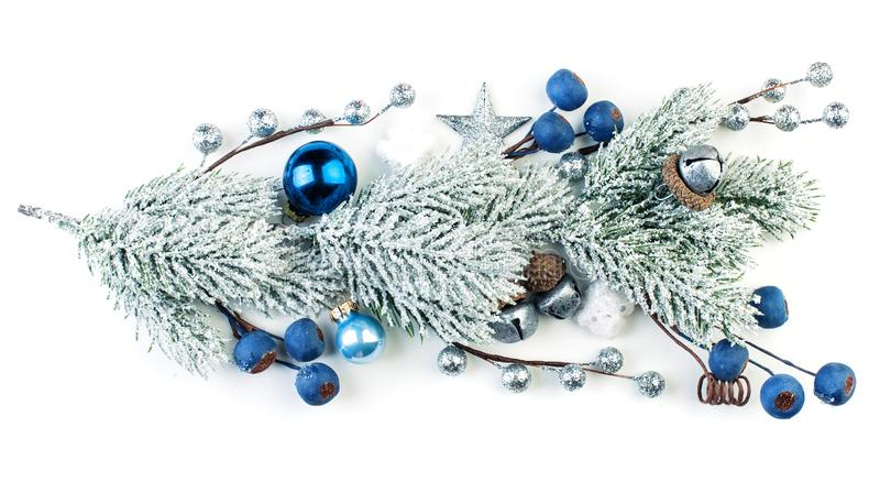 Christmas fir branch with winter frozen blue berries and baubles on white background stock images
