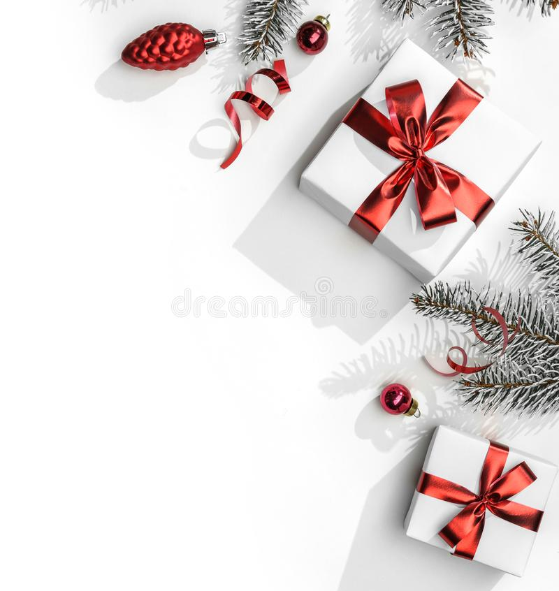Christmas fir branches with gift boxes with red ribbon on white paper background with bokeh, light. Xmas and New Year. Greeting card, winter holiday. Flat lay stock image