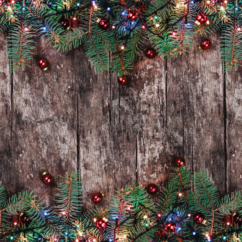 Christmas Fir branches with lights and red decorations on wooden background. Xmas and Happy New Year frame. Flat lay, top view. Copy space royalty free stock image