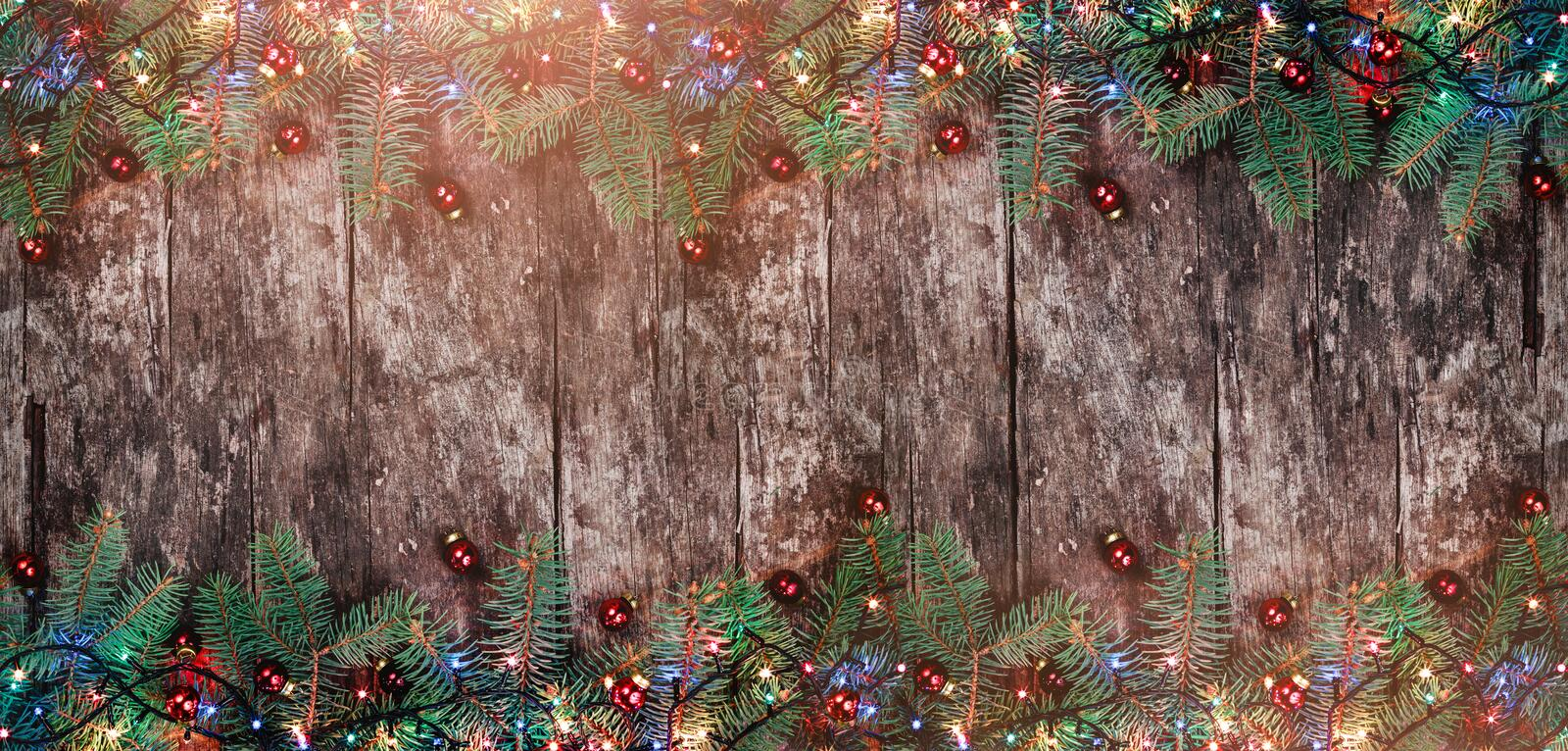 Christmas Fir branches with lights and red decorations on wooden background. Xmas and Happy New Year frame. Flat lay, top view. Copy space royalty free stock photo