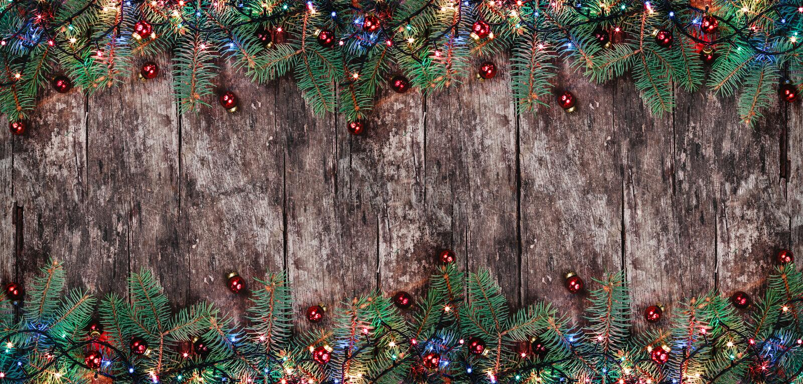 Christmas Fir branches with lights and red decorations on wooden background. Xmas and Happy New Year composition. Flat lay, top view. Copy space royalty free stock photography