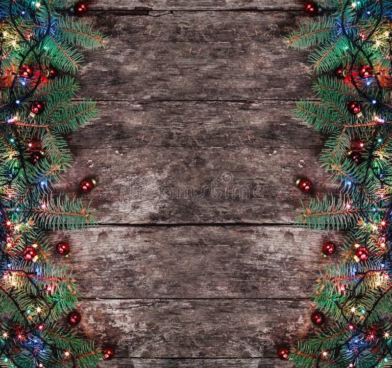 Christmas Fir branches with lights and red decorations on wooden background. Xmas and Happy New Year composition stock photography