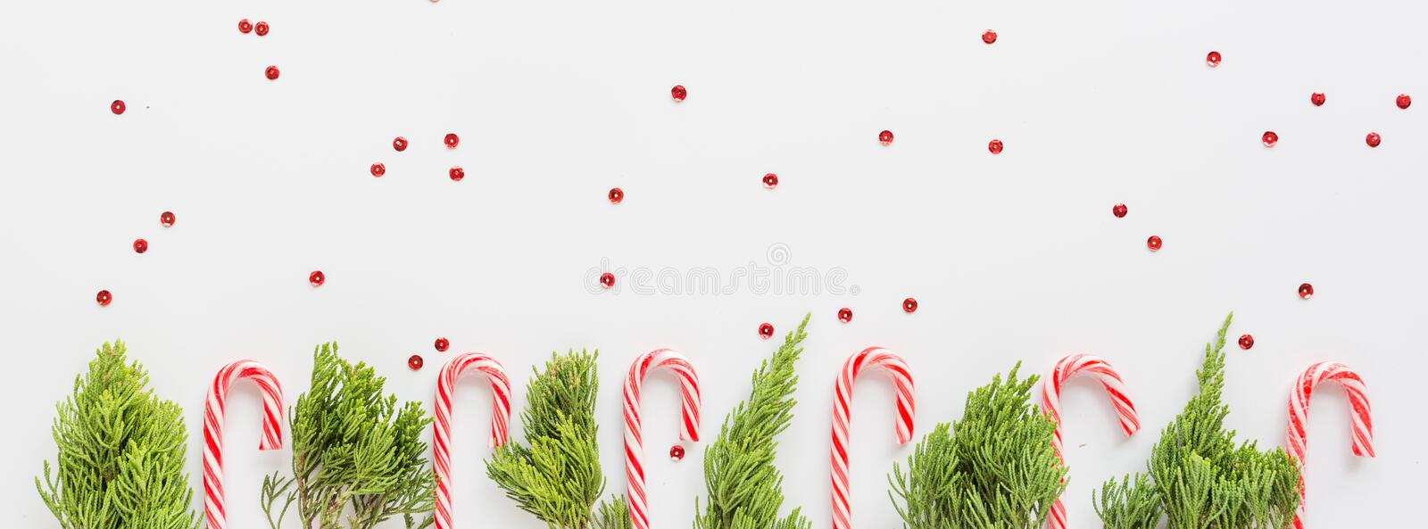 Christmas fir branches and lollipop canes on white. new year concept. Horizontal banner for web design. Greeting card, xmas royalty free stock photo