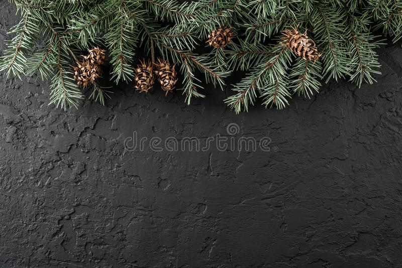 Christmas fir branches and pine cones on dark background with snowflakes. Xmas and New Year theme. Flat lay, top view, space for text, wide composition stock photography