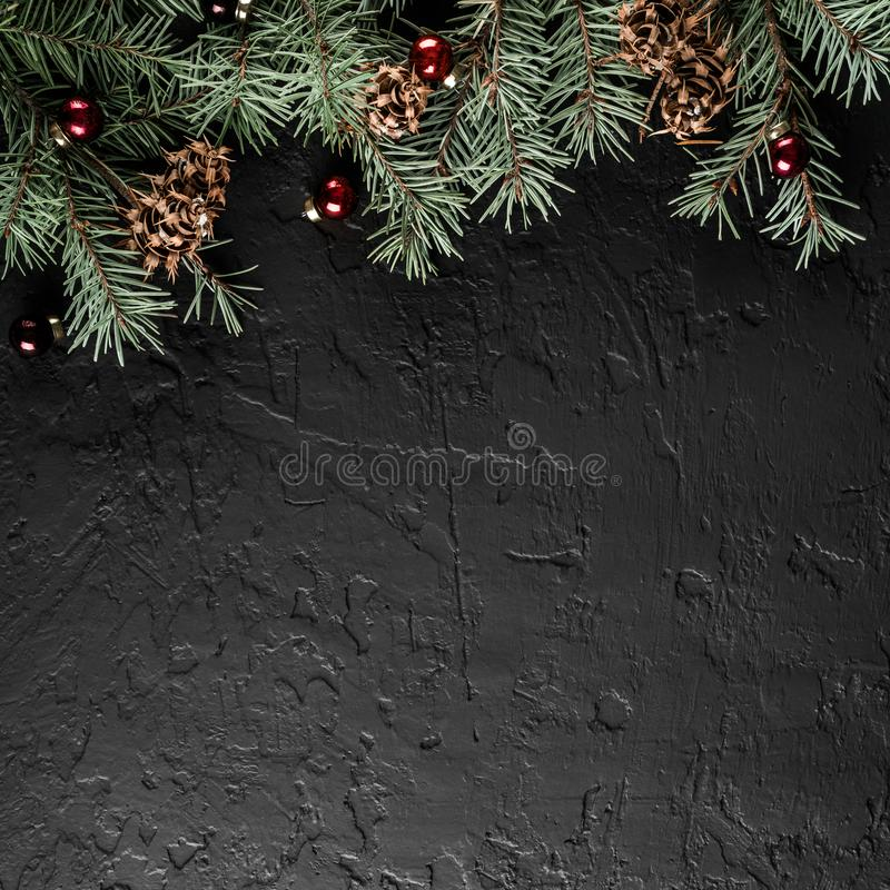 Christmas Fir branches with pine cones on dark black background. Xmas and Happy New Year card, bokeh, sparking, glowing. royalty free stock images