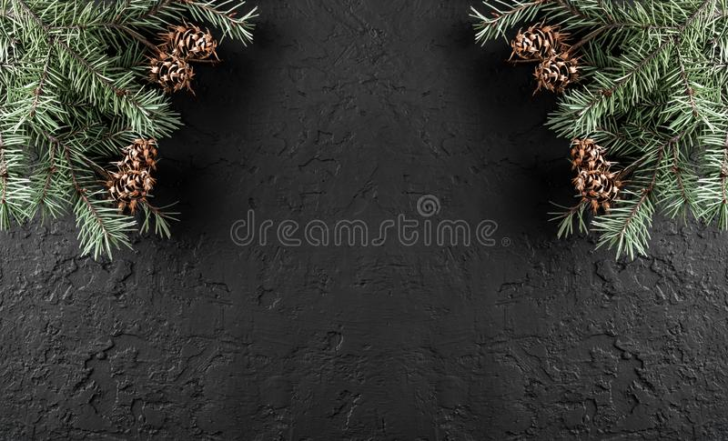 Christmas Fir branches with pine cones on dark holiday background with light. Xmas and Happy New Year theme. Flat lay, top view, wide composition stock photos