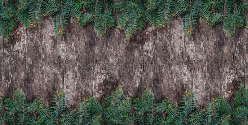 Christmas Fir branches on wooden background. Xmas and Happy New Year theme. Flat lay, top view, copy space, wide composition stock photo