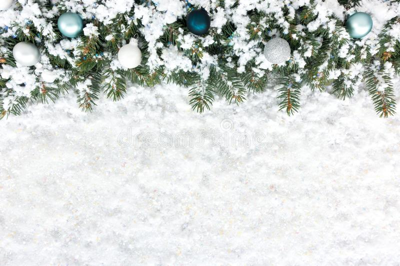 Christmas Fir Tree Border with Christmas Tree Baubles on Snow. Christmas background with Christmas fir tree border decorated with Christmas tree baubles and stock photography