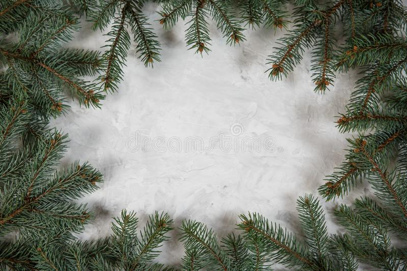 Christmas fir tree branch on stone background. Xmas backdrop. For your greeting card with space for text stock image
