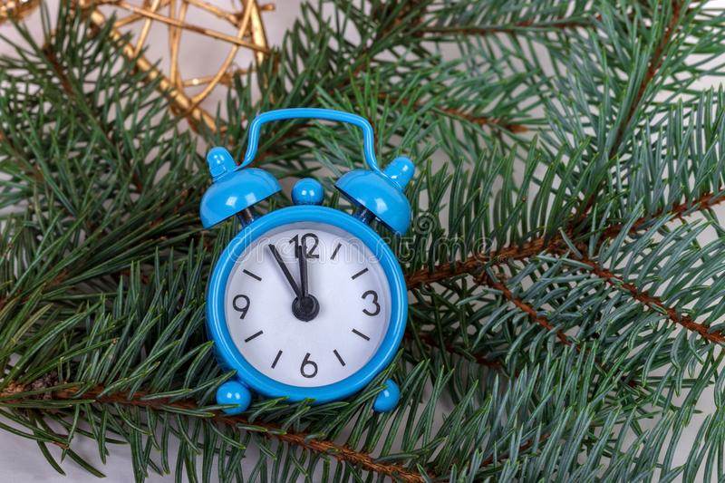Christmas fir tree branches with alarm clock on rustic wooden background with copy space royalty free stock photography