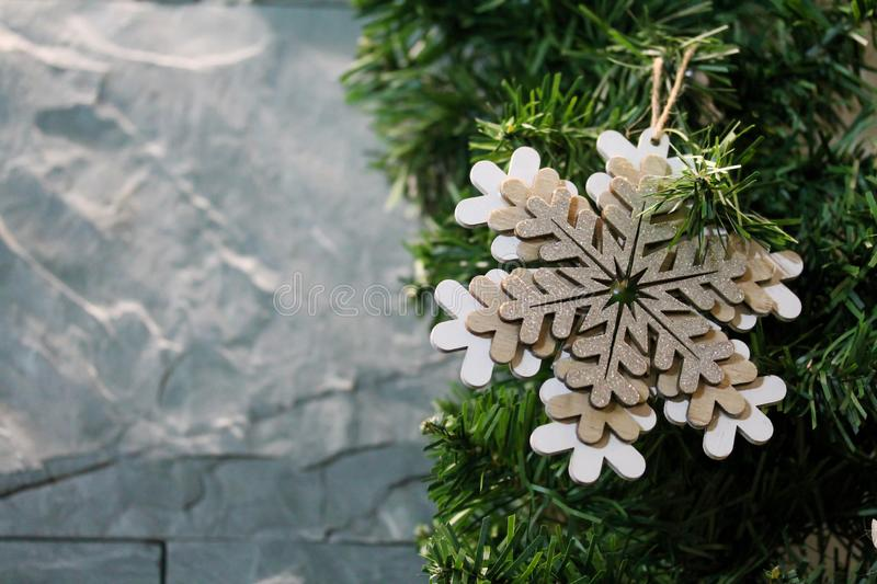 Christmas fir tree branches decorated with wooden figure of snowflake. Copy space for text. Gray stone wall background. Bright festive holiday decoration. New stock photo