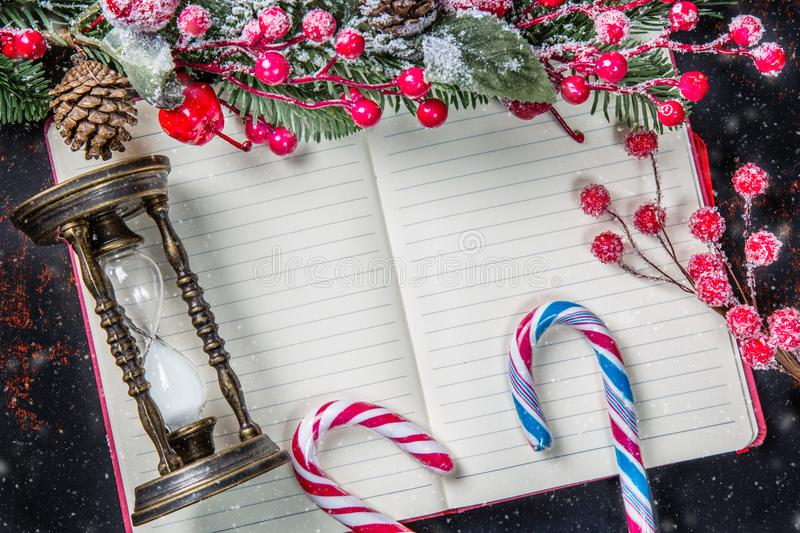 Christmas fir tree branches, decorations, candy canes, frozen red berries, cone and vintage hourglass frame on notebook with snow,. Copy space for text. Can be royalty free stock photos