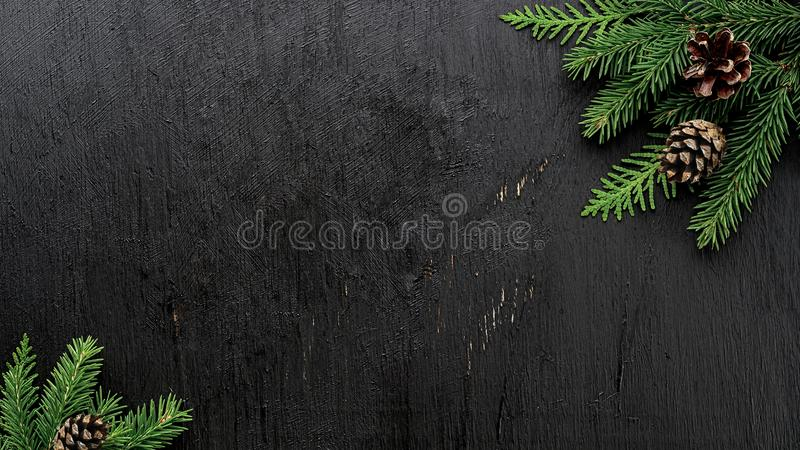 Christmas Fir tree branches and pine cones on a black wooden board royalty free stock photo