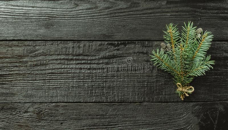 Christmas fir tree branches and pine cones on wooden dark, black background stock photo