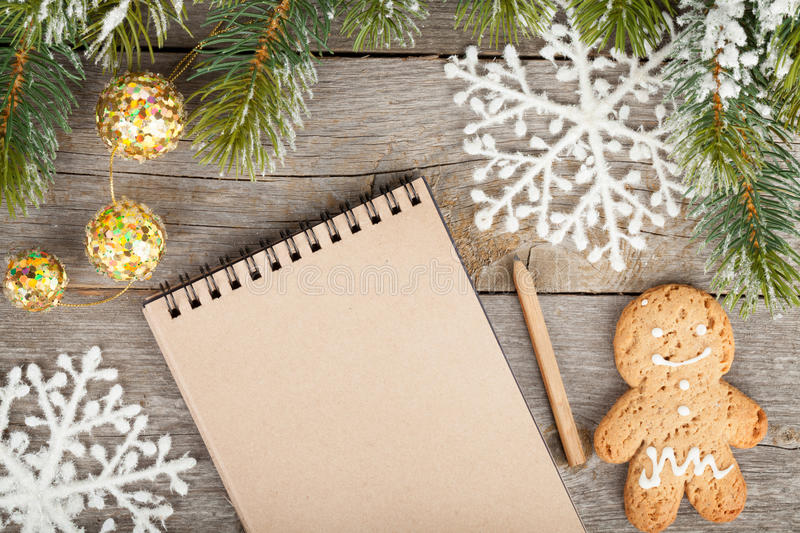 Christmas fir tree, decor and blank notepad on wooden board back stock images