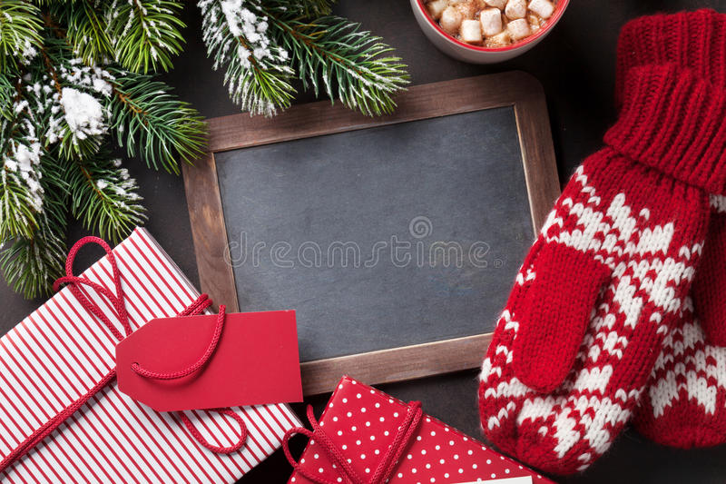 Christmas fir tree, gift, mittens and chalkboard royalty free stock photos