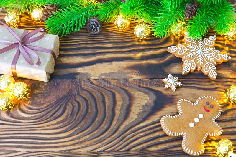 Christmas fir tree with homemade gingerbread cookies, gift and lights on old wooden background with space for text. Merry Christma royalty free stock photography