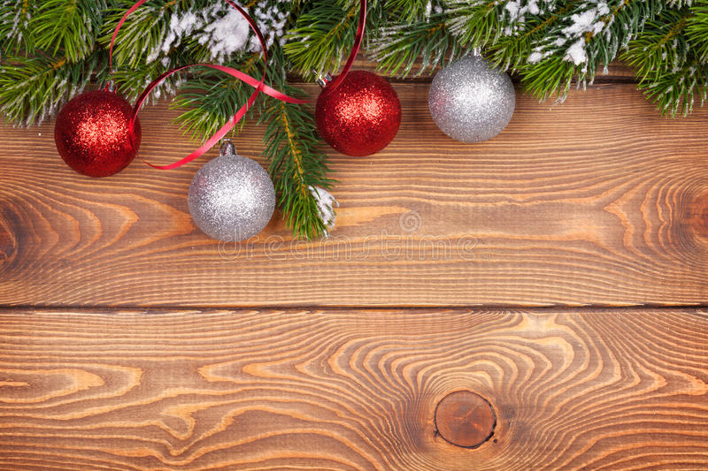 Christmas fir tree with snow and baubles on rustic wooden board stock photo
