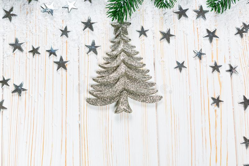 Christmas fir tree in snow with silver stars on white wooden background stock photos
