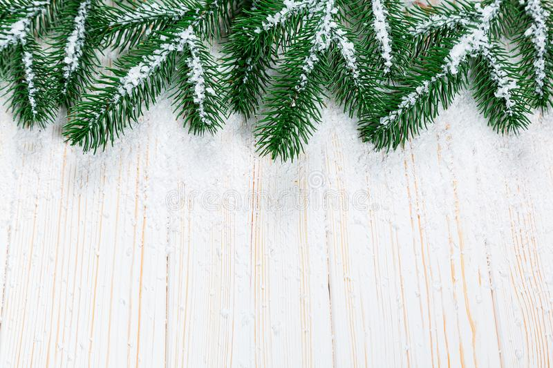 Christmas fir tree with snow on white wooden background. royalty free stock photography
