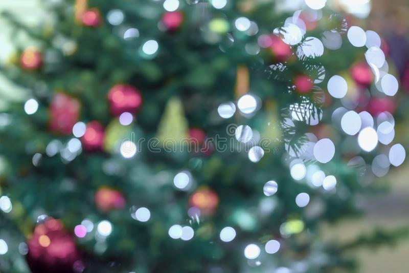 Christmas Fir tree, spruce with silver bokeh, unfocused sparkles of garland, decor lights. Abstract festive background royalty free stock photo